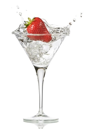 fresh splashing strawberry into a martini glass