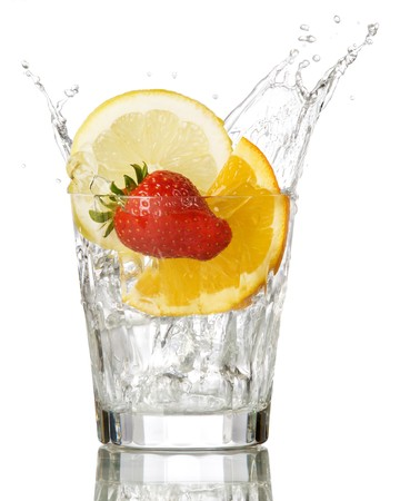 splashing orange, lemon and strawberry into a water glass Stock Photo