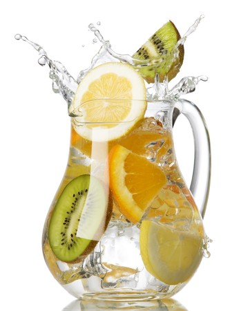 splashing orange, lemon and kiwi into a water glass Stock Photo