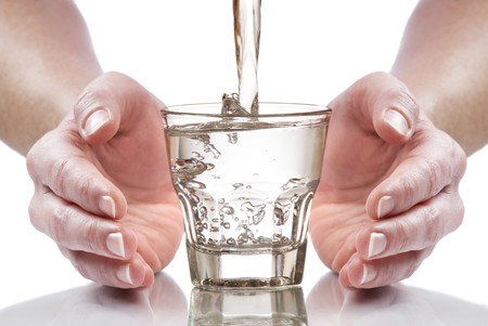 glass of fresh water between hands close up
