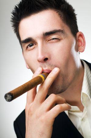 hombre fumando puro: joven hombre de negocios de fumar cigarro cerca disparar