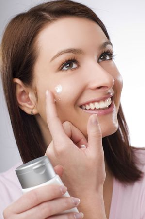 young brunette woman applying creme on her face