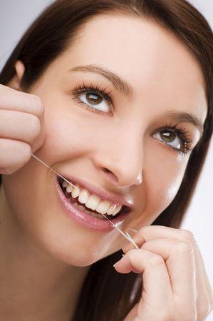 flossing: young Woman flossing teeth close up shoot