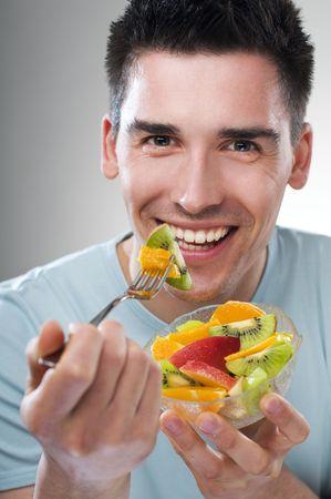 hombre comiendo: comer fruta joven de cerca disparar Foto de archivo