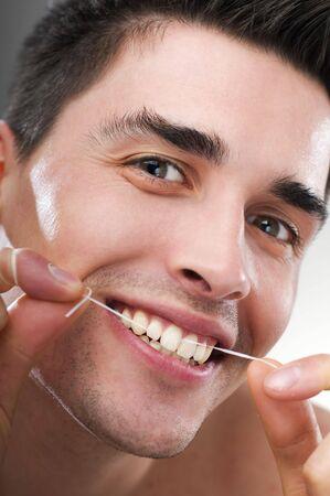 flossing: young man flossing teeth close up shoot Stock Photo