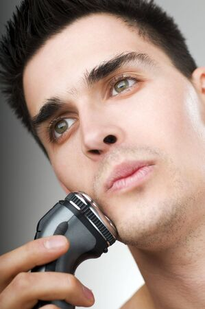 trimming: young man shaving his beard off with an electric razor Stock Photo