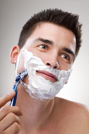 hombre afeitandose: Hombre joven con navaja de afeitar cerca
