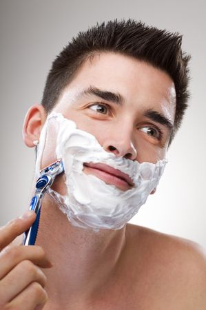 young Man shaving with razor close up Stock Photo
