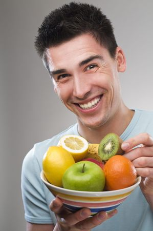 young man with bowl of  fruit close up shoot photo