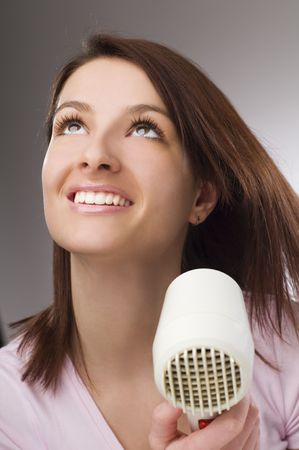 Beautiful woman drying her hair with hairdryer photo