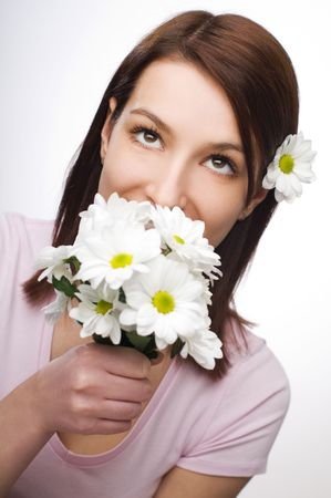 Beautiful young woman smelling flowers close up photo