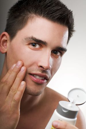DERMATOLOGY: Young handsome man applying creme close up