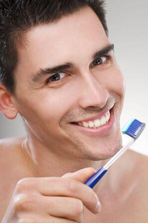 Young man brushing teeth close up shoot