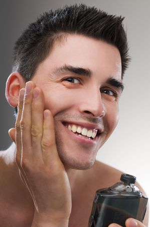 shaving blade: Young man applying after shave close up Stock Photo