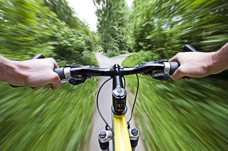 action blur: Mountain biking down hill descending fast close up Stock Photo