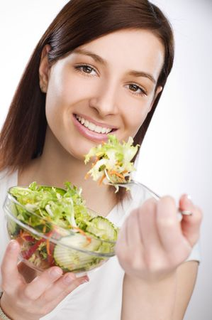 Young attractive woman eating salad close up photo