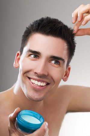 Young handsome man applying hair gel close up photo