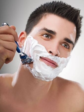 Young Man shaving with razor close up photo