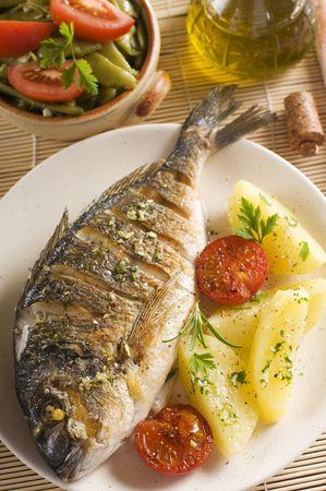 Rôti de poisson doré avec des pommes de terre et (ail, persil) sauce. Banque d'images