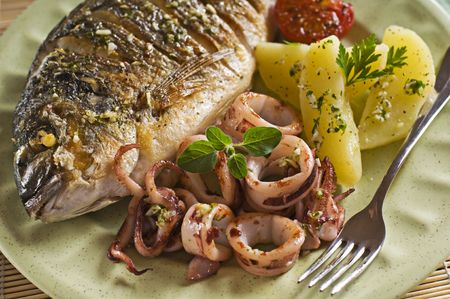 Roasted fish and squid with potatoes close up photo