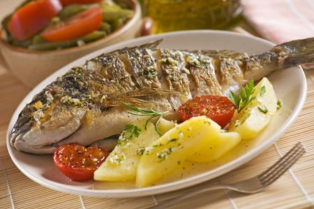 bream: Roasted gilt fish with potatoes and (garlic, parsley) sauce Stock Photo