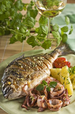Roasted fish and squid with potatoes close up Stock Photo - 5210549