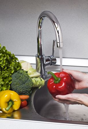 carot: Woman washing red pepper in kitchen close up