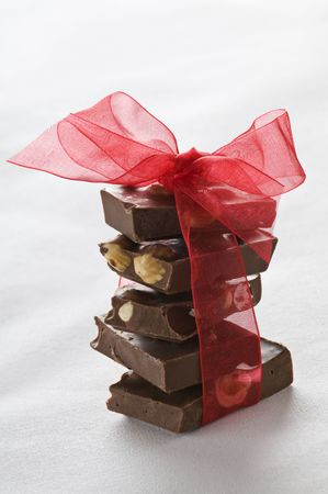 chocolate block: Stack Of Chocolate Pieces with red bow close up