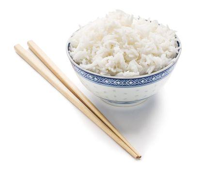 arroz chino: Bol de arroz cocido con palillos aislados sobre fondo blanco