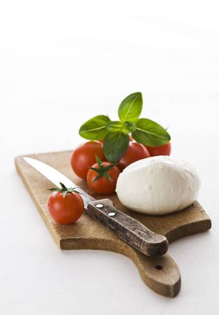 Fresh mozzarella, tomato and basil on wooden board photo