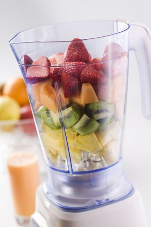 Mixed fresh fruit in blender close up Stock Photo