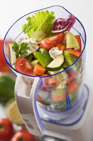 Sliced fresh vegetables in blender close up shoot Stock Photo