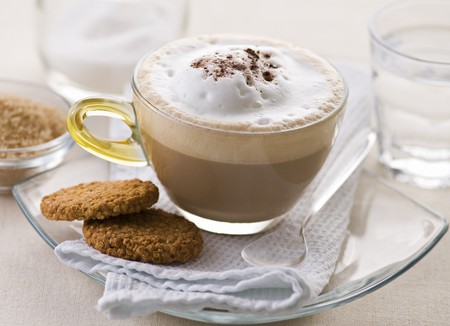Fresh cappuccino in glass with cookie close up