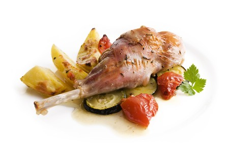 Roasted rabbit leg with potato and vegetables close up Stock Photo