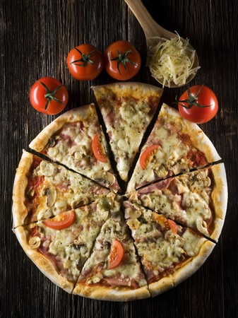 pizza background: Sliced fresh pizza on wooden background close up