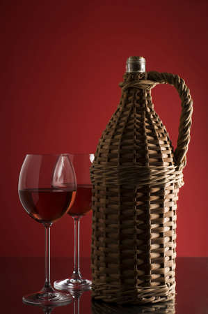 Bottle with red wine and glass close up photo