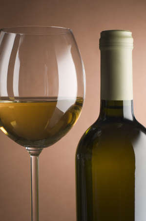 Bottle with white wine and glass close up photo