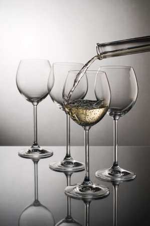 White wine pouring into glass close up 