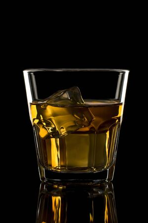 whiskey: Glass of whiskey with ice on black background