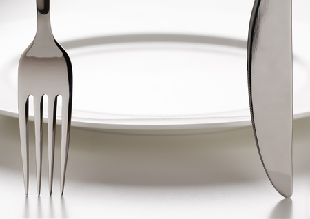 Fork and knife infront of white plate close up Stock Photo - 8991931
