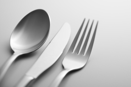silver flatware: Spoon fork and knife in shallow focus close up