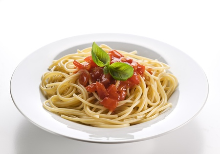 eating pasta: Spaghetti with tomato sauce and basil close up Stock Photo