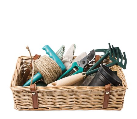 Gardening basket with tools isolated on white photo