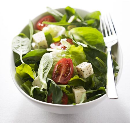spinach: Fresh mixed green salad with mozzarella and tomatoes Stock Photo