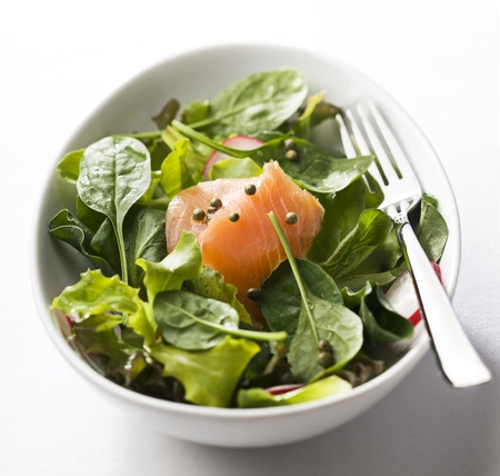 Fresh green salad with smoked salmon close up photo