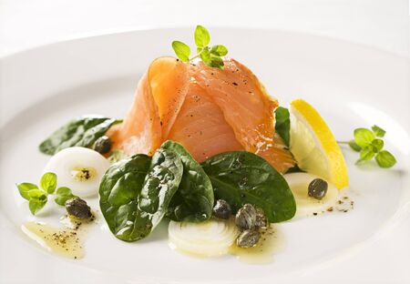 Smoked salmon with spinach, capers, and spring onions close up photo