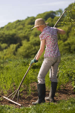 Young woman with hat raking the garden outdoor photo