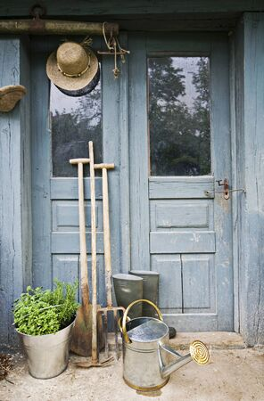 Gardening tools infront of old house doors Stock Photo