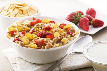 cereal bowl: Fresh corn flakes with strawberries and milk close up