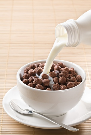 milk pouring: Milk pouring on chocolate cereal balls close up